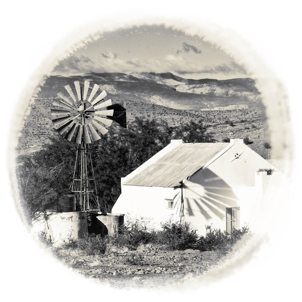 old Karoo farmhouse with windmill and mountains
